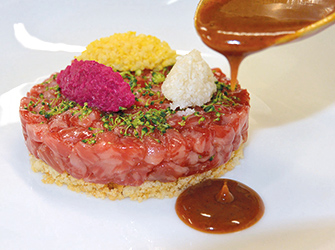 Wagyu topside like a tartare, beaufort crumble, basted in langoustine juice and cauliflower sauce.
