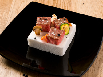 Cubes of Wagyu served on a tile of sweet salt from Cervia, a plate of vegetables and black garlic