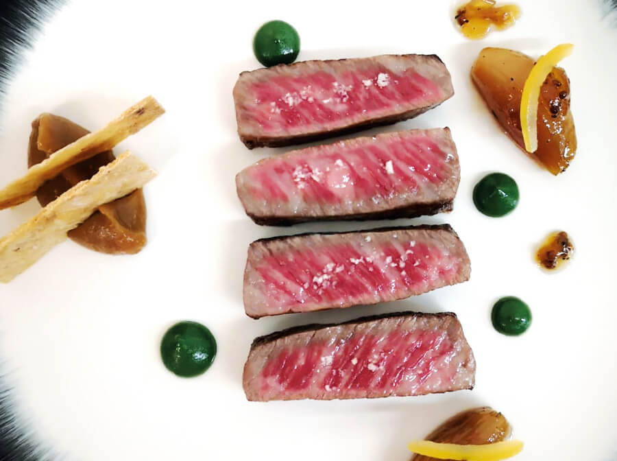 Grilled wagyu beef, served with grilled shallots, coffee, pears, parsley oil and crispy bacon