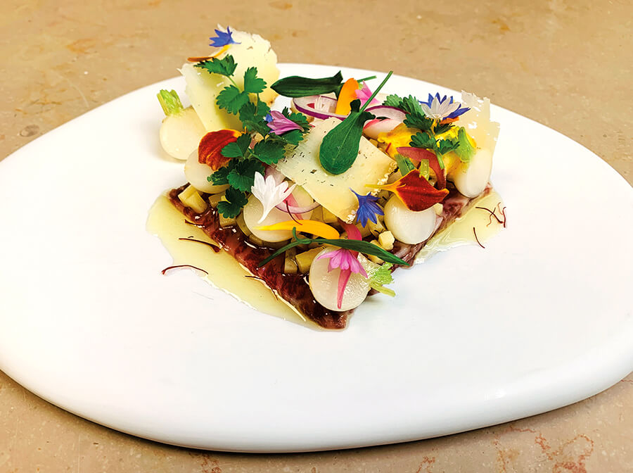 Japanese wagyu beef top round as a carpaccio, served with natsu komachi turnips in vinaigrette with a virgin oil flavoured with Burgundy saffron, and cow's milk Tomme from Blanot, and piquant herbs.